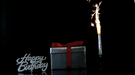 doğum günü : Sparkler burning beside gift and happy birthday sign on black background Stok Video