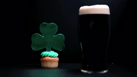 queque : Pint of stout and st patricks day cupcake on black background