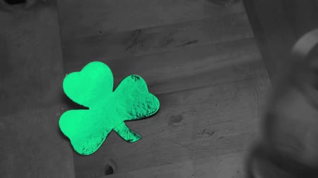 st patrick : Hand putting down empty pint beside large green shamrock in selective black and white Stock Footage