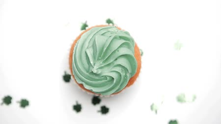 queque : St patricks day cupcake turning with green shamrock confetti falling on white surface