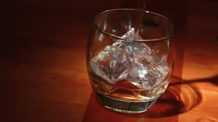 viski : Tumbler of ice being filled with whiskey on wooden surface