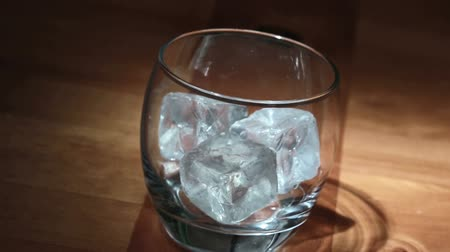 whisky : Hand putting ice into tumbler then pouring whiskey on wooden table Wideo