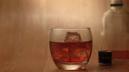паб : Cigar being smoked beside tumbler of whiskey on the rocks on a wooden surface with bottle in background