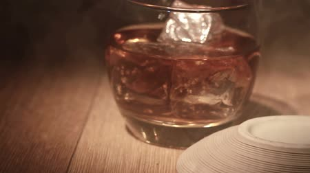 cygaro : Cigar being placed beside tumbler of whiskey on the rocks on wooden surface Wideo
