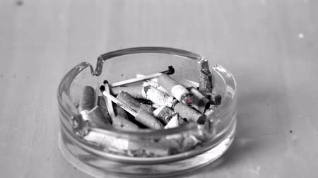 carcinogenic : Cigarette falling in ashtray in slow motion Stock Footage