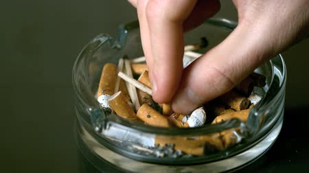 cigarettes : Hand putting cigarette out in ashtray in slow motion