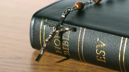 jehovah witness : Rosary beads falling onto bible on a table in slow motion Stock Footage