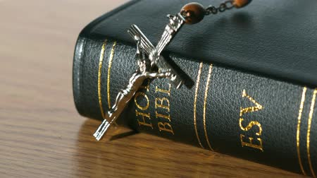 jehovah witness : Rosary beads falling onto black bible in slow motion Stock Footage
