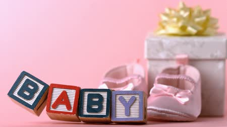 booties : Baby blocks toppling over in front of booties and gift box in slow motion