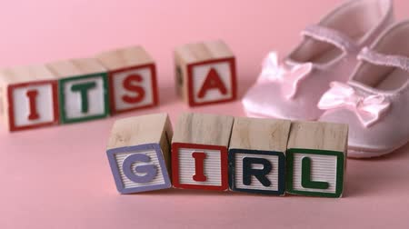 booties : Its a girl message in letter blocks beside pink booties in slow motion
