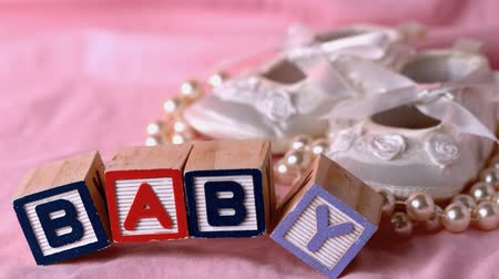 booties : Baby in letter blocks beside booties and pearls on pink blanket in slow motion