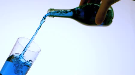 coquetel : Blue liquid pouring into glass low angle in slow motion