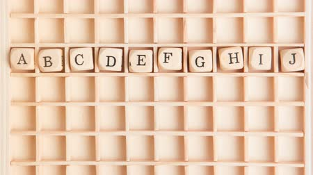 abeceda : Hand spelling out the alphabet in wooden dice on a grid in stop motion