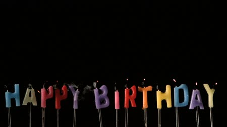 doğum günü : Colourful happy birthday candles being extinguished in slow motion
