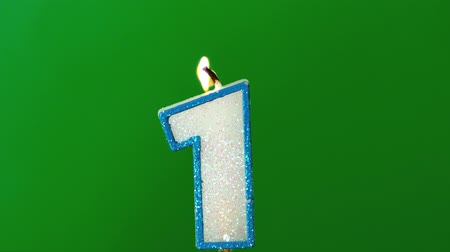 oŚwietlenie : One birthday candle flickering and extinguishing on green background in slow motion