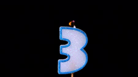 extinguishing : Three birthday candle flickering and extinguishing on black background in slow motion