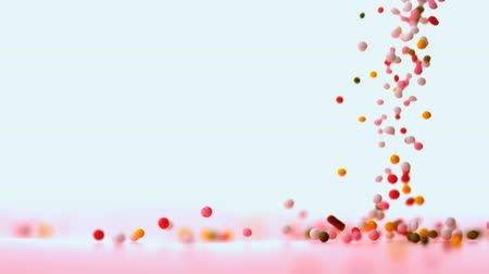 colorful candy : Sprinkles pouring onto pink surface in slow motion