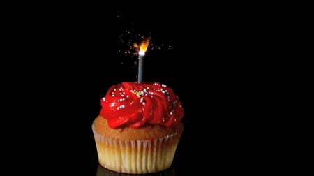 queque : Sparkler burning on red birthday cupcake in slow motion