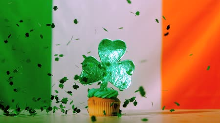jegesedés : Shamrock confetti falling on st patricks day cupcake on irish flag background in slow motion