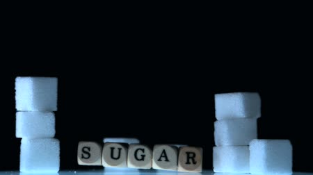 диабет : Dice spelling out sugar falling beside sugar cubes in slow motion