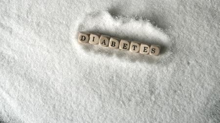 диабет : Dice spelling diabetes falling into pile of sugar in slow motion