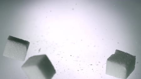 диабет : Sugar cubes falling onto white surface in slow motion