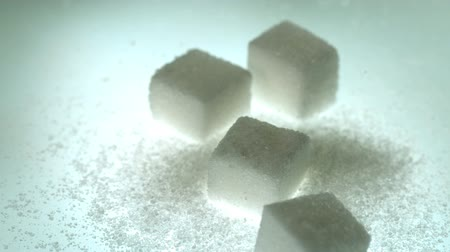 kavramsal : Sugar cube falling onto pile of cubes and powder sugar in slow motion Stok Video