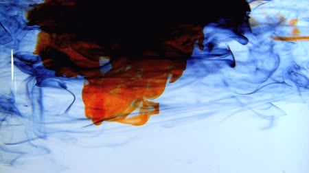 yellow ink : Blue orange and black ink swirling in water in slow motion