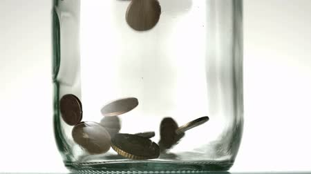 mince : Many coins pouring into glass jar close up on white background in slow motion