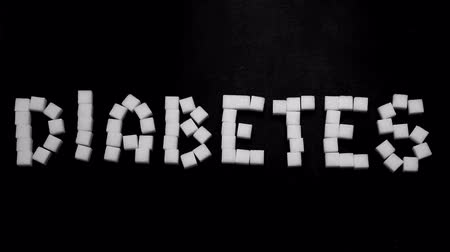 диабет : Hand pushing away diabetes spelled in sugar cubes on black background