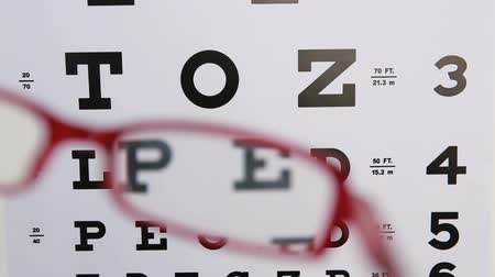 фокус : Red glasses held up to read eye test for optician