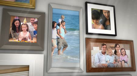 çerçeveler : Montage of families having fun together presented in picture frames on grey wall Stok Video