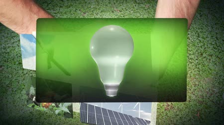 энергия ветра : Montage of energy efficiency clips coming from globe held in hand