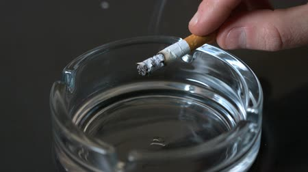 popel : Hand tipping ash into empty ashtray in slow motion