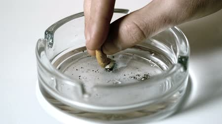 carcinogenic : Hand extinguishing cigarette in empty ashtray in slow motion