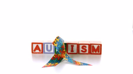 fitas : Awareness ribbon falling onto blocks spelling autism on white background in slow motion
