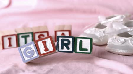 booties : Its a girl message in letter blocks beside booties on pink blanket in slow motion Stock Footage
