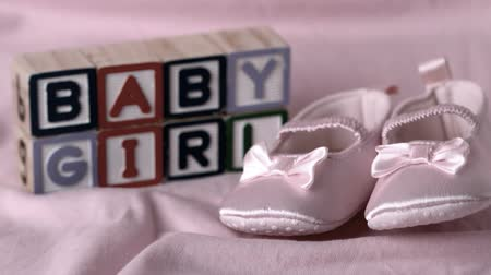 booties : Baby booties falling on pink blanket with baby girl message in blocks in slow motion