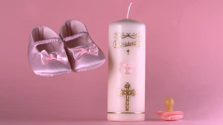 christening : Baby shoes falling beside baptism candle and pacifier in slow motion