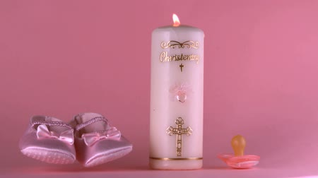 booties : Baby shoes falling beside lit baptism candle and pacifier in slow motion