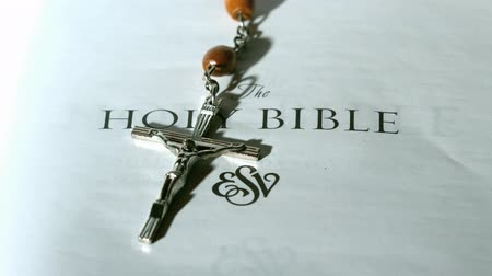 jehovah witness : Rosary beads falling onto first page of bible in slow motion