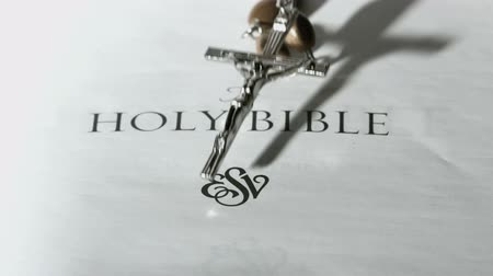 jehovah witness : Rosary beads falling onto first page of holy bible in slow motion
