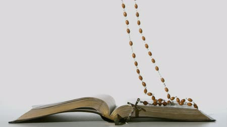jehovah witness : Rosary beads falling onto open bible on white background in slow motion Stock Footage