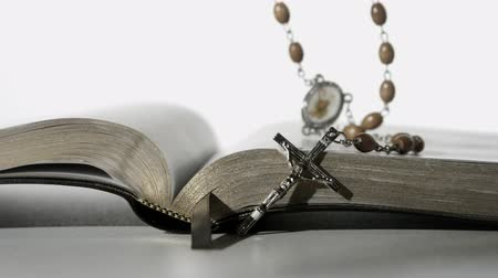 jehovah witness : Rosary beads falling onto open bible on white background close up in slow motion