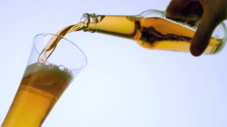 piwo : Hand pouring bottle of beer into glass in slow motion