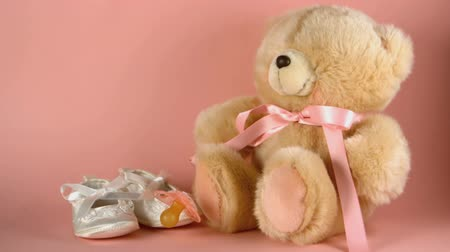 booties : Pink soother falling onto a teddy bear and baby shoes in slow motion Stock Footage