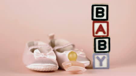booties : Pink soother falling in front of baby shoes and blocks spelling baby in slow motion