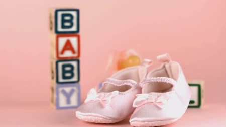 booties : Pink baby shoes falling in front of blocks spelling baby and girl in slow motion Stock Footage