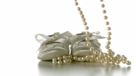 gyöngyszem : Pearl necklace falling onto baby shoes in slow motion