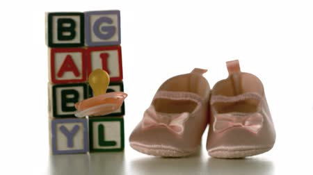 booties : Yellow soother falling besides baby blocks and booties in slow motion